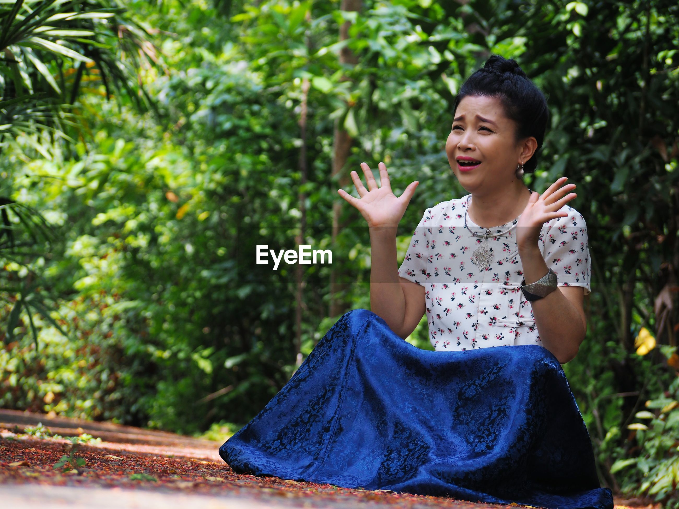 Happy woman gesturing while sitting on field in forest