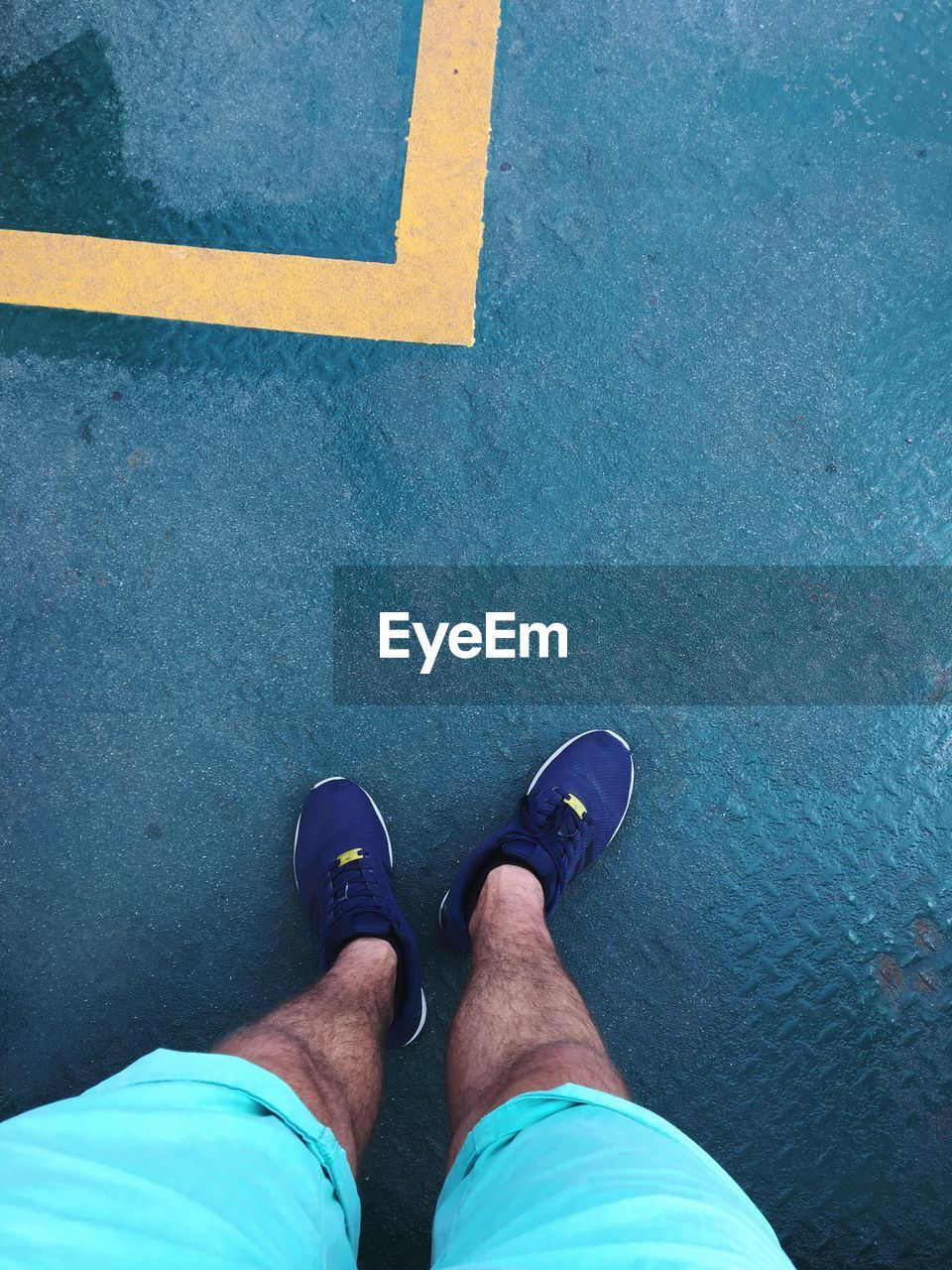 low section, human leg, shoe, body part, human body part, personal perspective, real people, one person, high angle view, standing, lifestyles, men, day, leisure activity, city, street, road, outdoors, blue, human foot, human limb, jeans, shorts