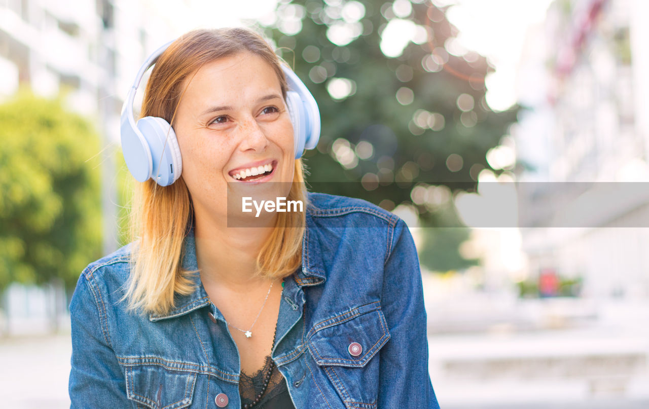 Cheerful young woman looking away while listening music in city