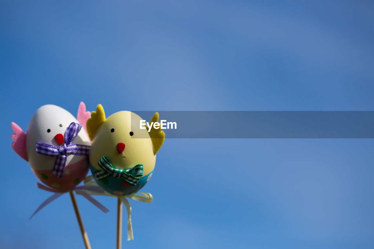 copy space, blue, representation, animal representation, sky, no people, nature, low angle view, art and craft, close-up, clear sky, yellow, toy, celebration, balloon, animal, studio shot, still life, focus on foreground, egg, blue background