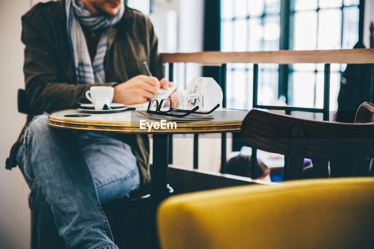 Man writing while sitting on chair in cafe