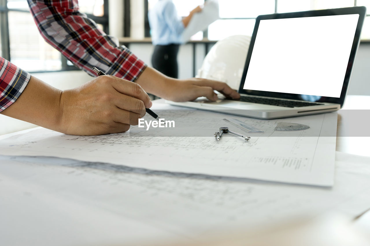 human hand, indoors, one person, pen, hand, human body part, occupation, plan, real people, table, adult, men, office, working, laptop, communication, wireless technology, computer, paper, design professional, using laptop, blueprint, architect