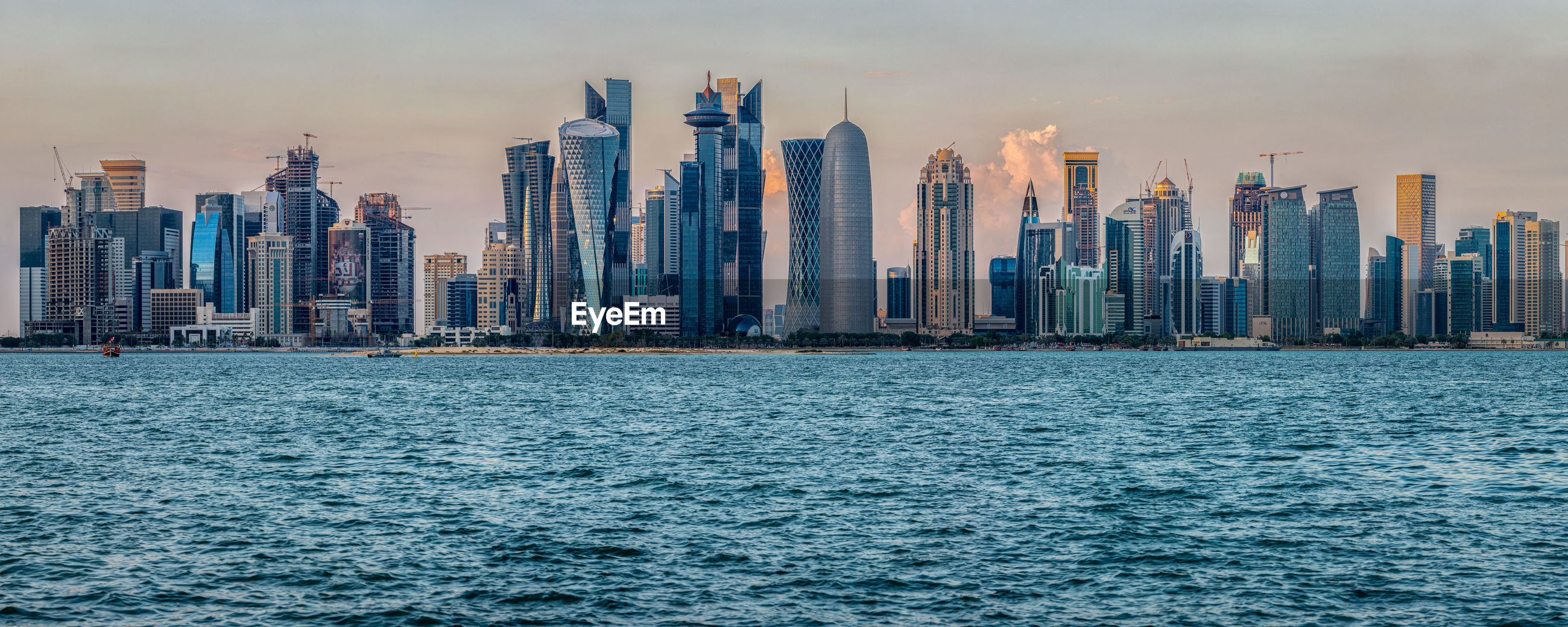 Doha skyline daylight view with arabic gulf in foreground and clouds in the sky in background