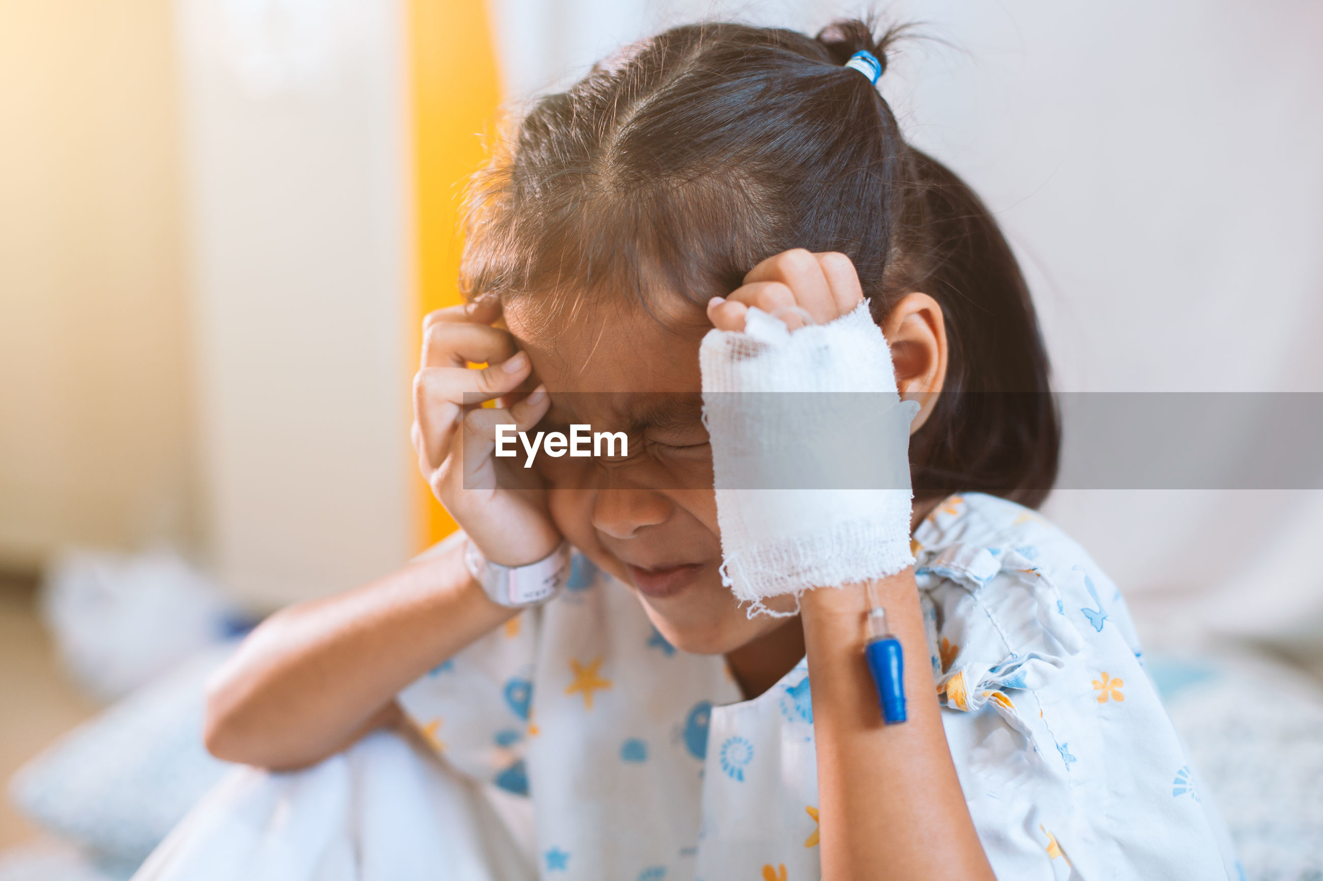 Close-up of girl with headache sitting in hospital
