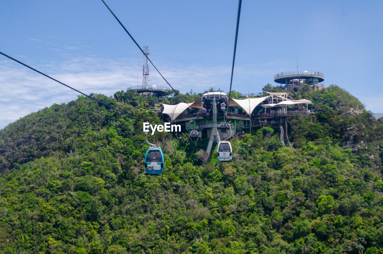 mode of transportation, plant, transportation, tree, sky, cable car, nature, no people, day, travel, growth, cable, overhead cable car, green color, architecture, built structure, outdoors, land vehicle, mountain, foliage