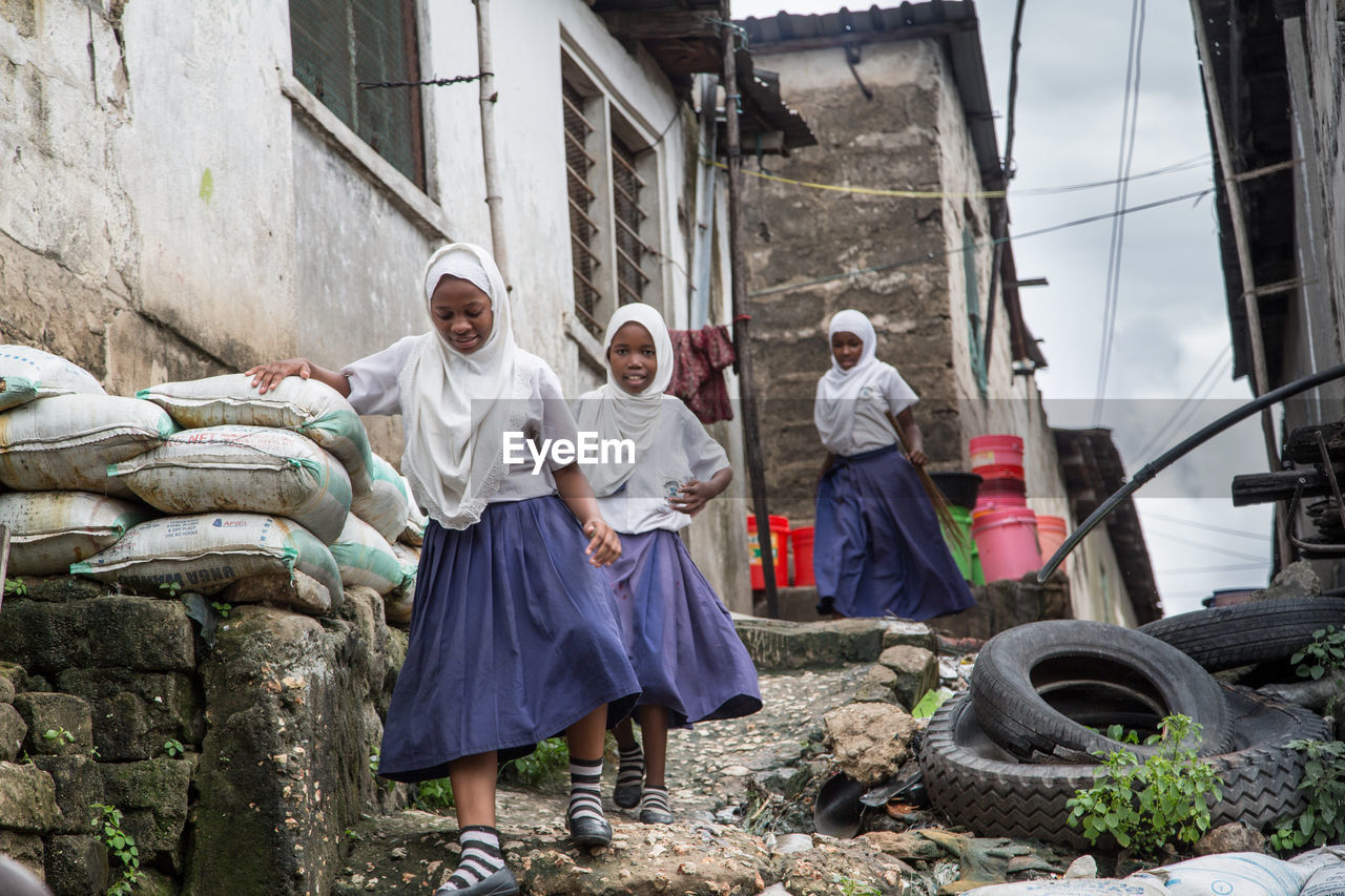 Girls in uniform walking amidst houses at village
