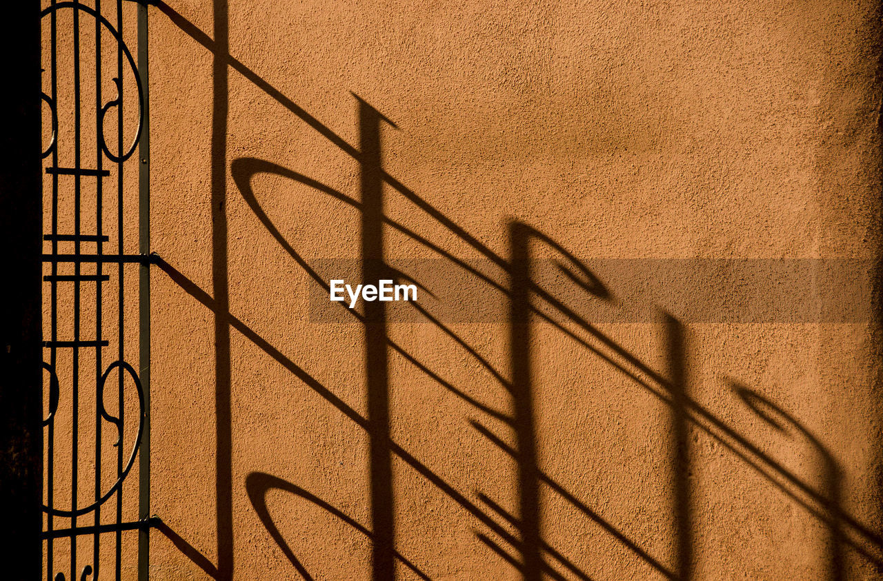 Shadow of fence on brown wall