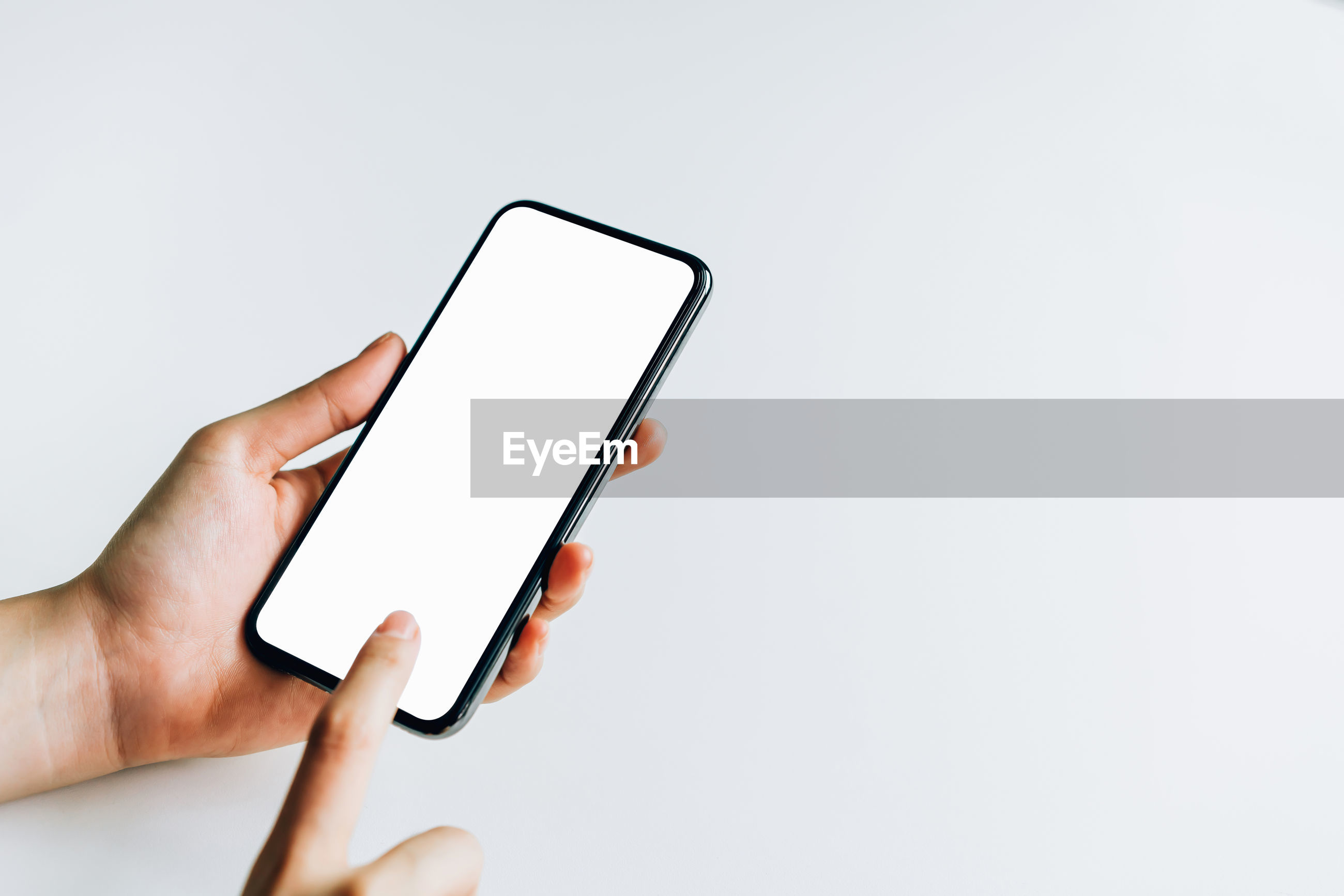 Midsection of person holding mobile phone over white background