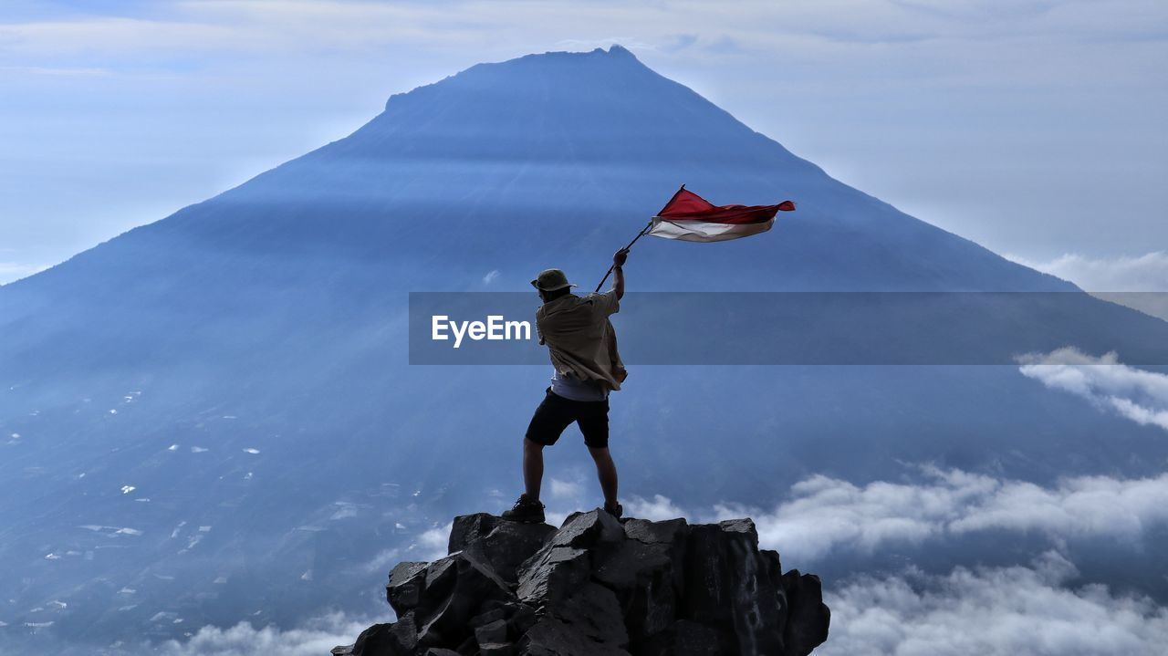 Rear view of man holding flag while standing on rock against sky