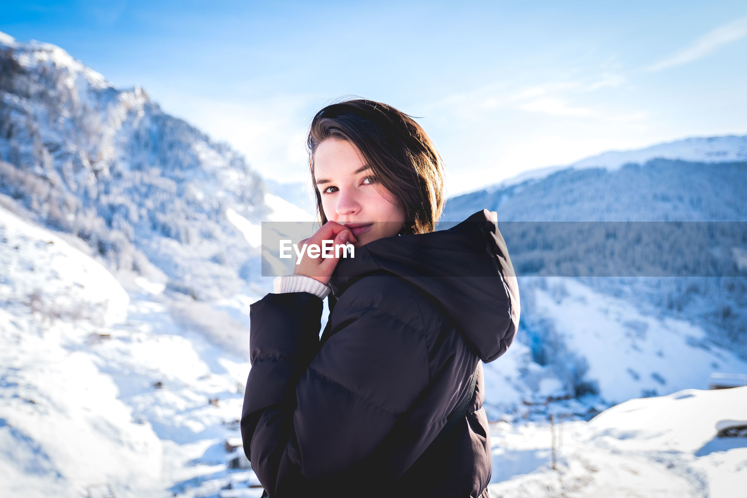 Young woman standing on snow covered mountain