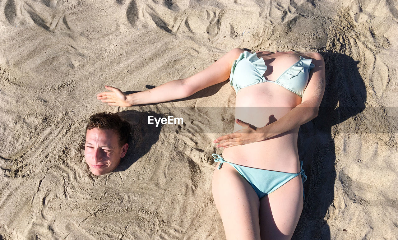 High angle view of friends relaxing on sand at beach