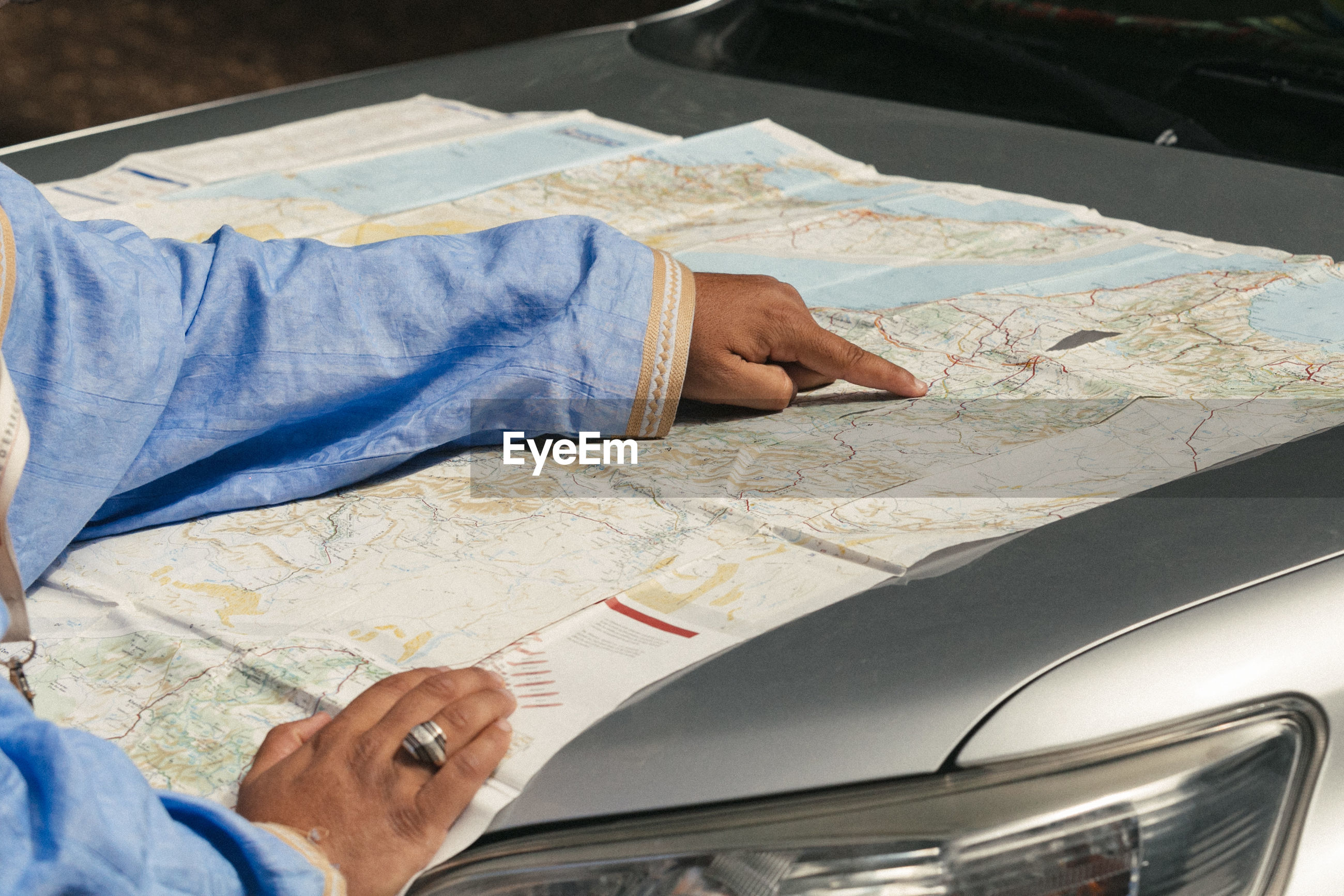 Cropped hands with map on car hood