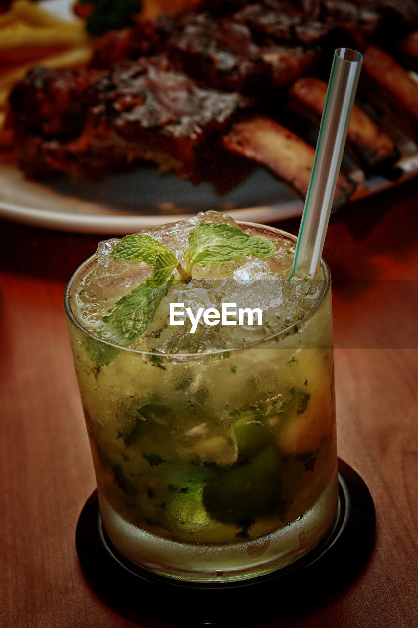 food and drink, drinking glass, refreshment, table, drink, cocktail, close-up, freshness, drinking straw, mint leaf - culinary, alcohol, mojito, focus on foreground, cold temperature, ice cube, indoors, no people, food, ready-to-eat, day