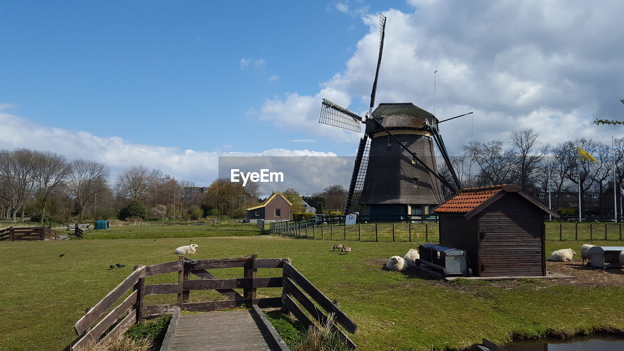 TRADITIONAL WINDMILL ON FIELD BY ROAD AGAINST SKY