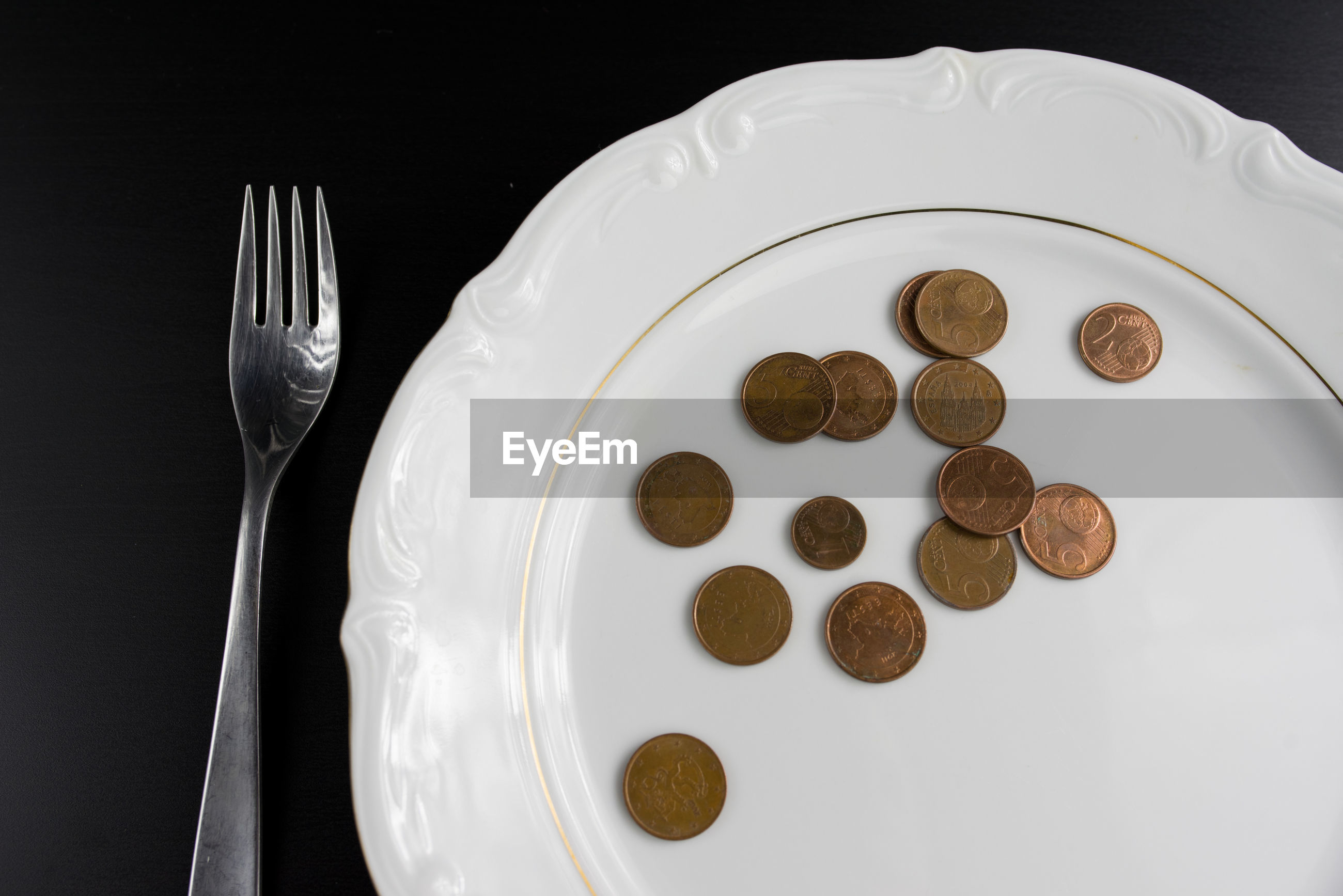 Close-up of coins in plate over black background