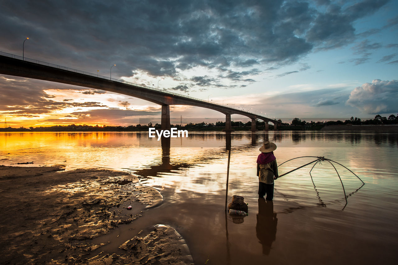 Man Fishing In River Against Bridge During Sunset