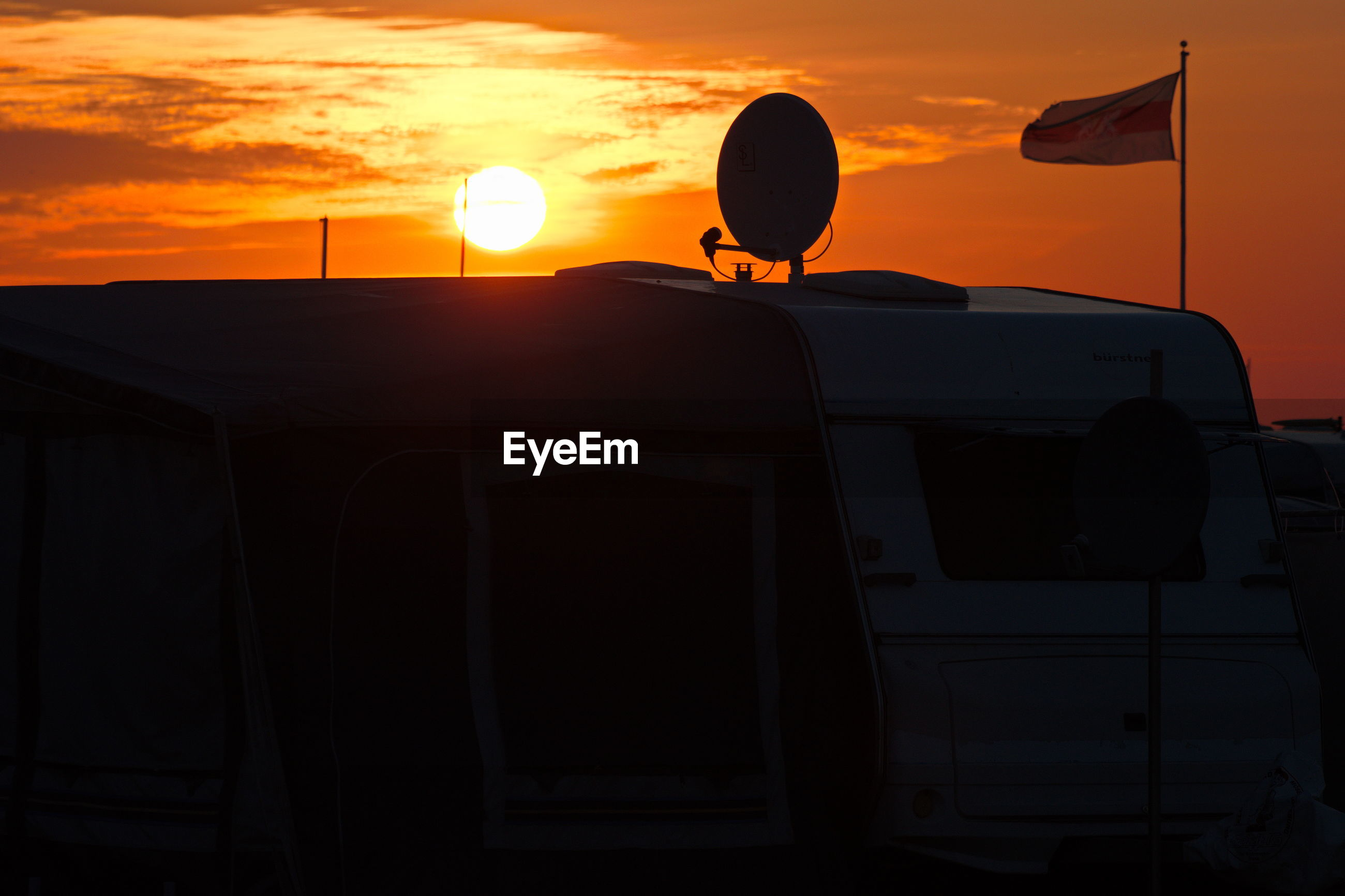 Flag and satellite dish on motor home against sky during sunset