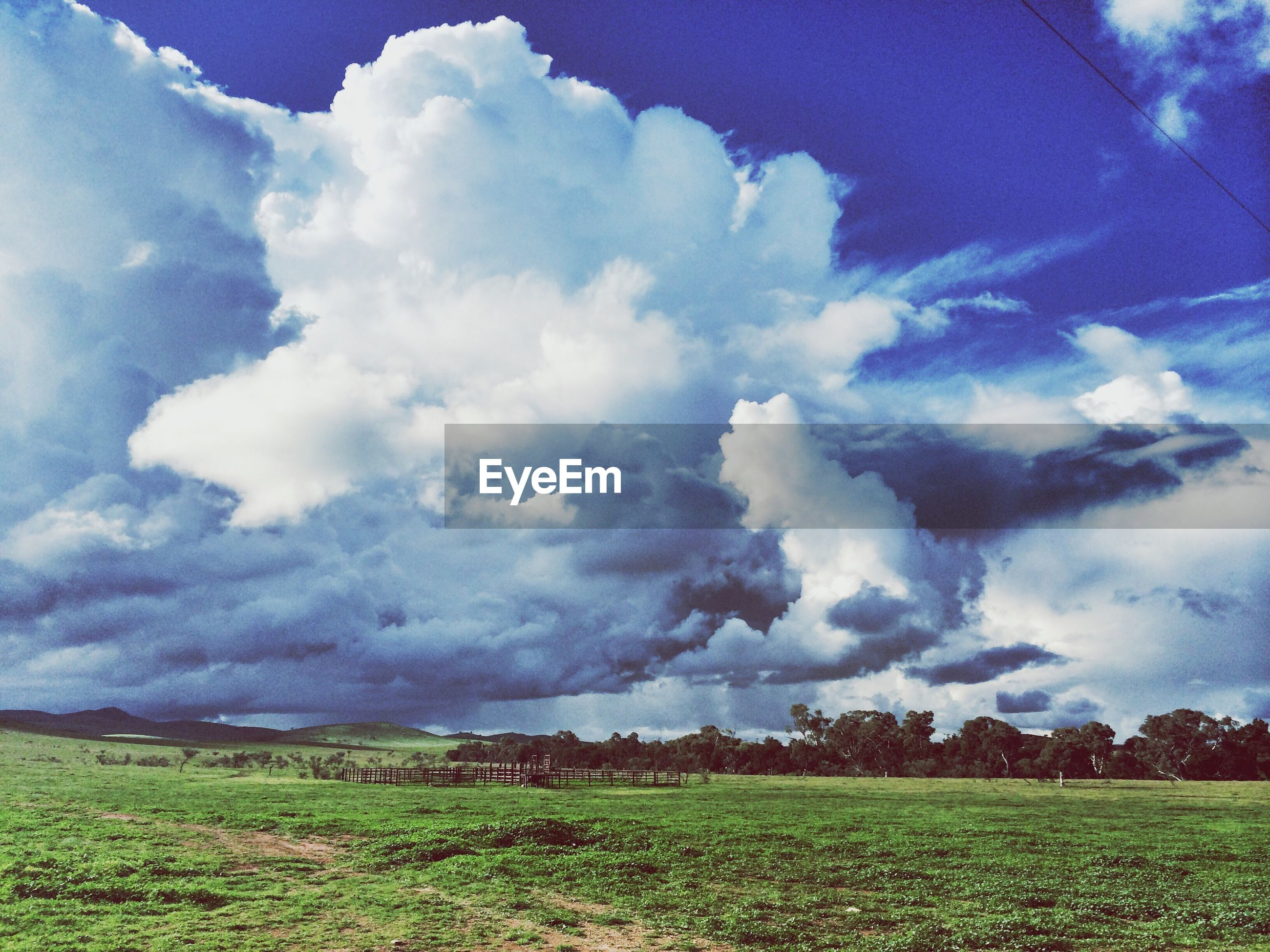 sky, cloud - sky, field, landscape, tranquil scene, grass, tranquility, cloudy, scenics, beauty in nature, cloud, nature, rural scene, green color, grassy, growth, blue, idyllic, agriculture, day