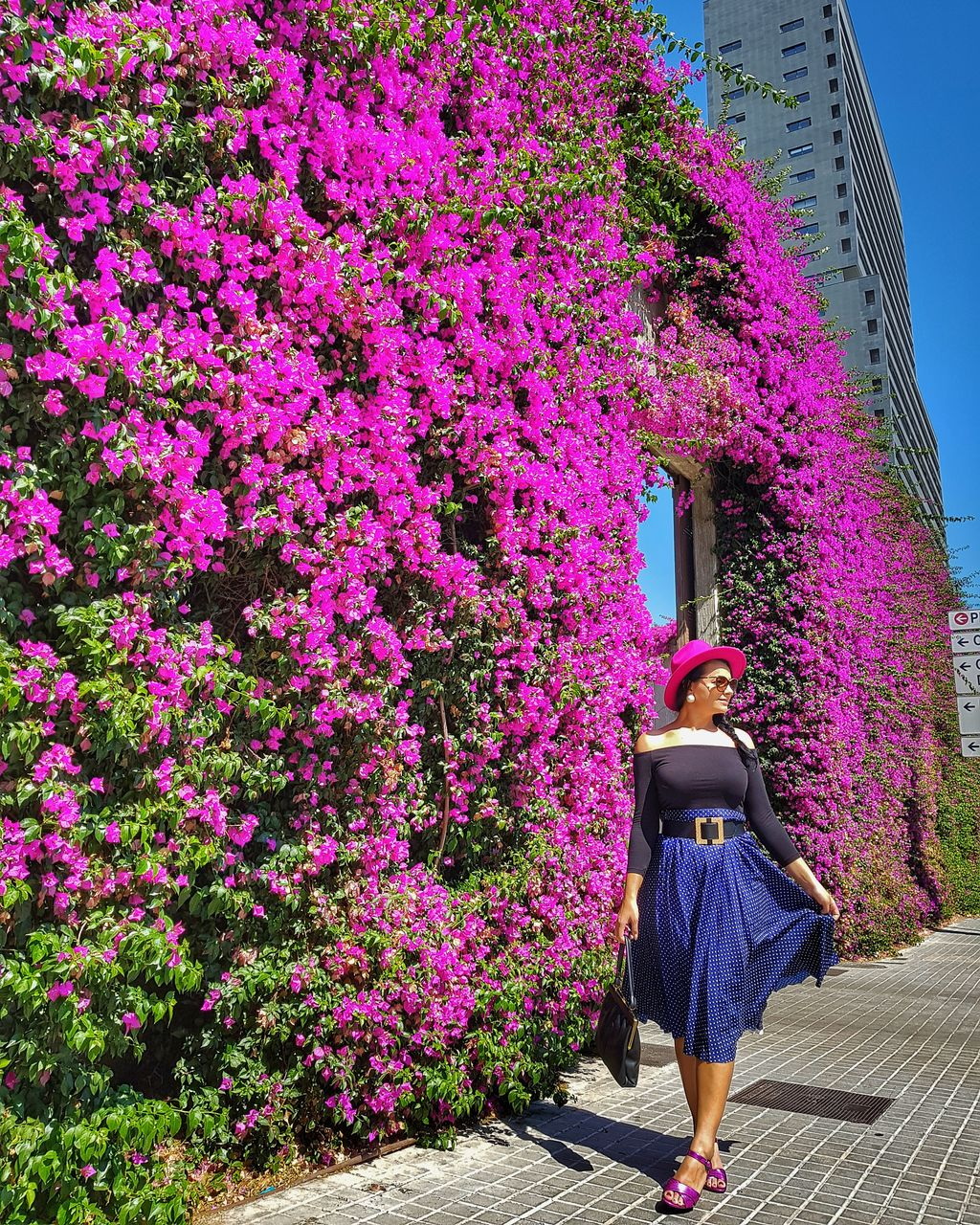 Young woman walking on footpath by wall covered with pink flowering plants