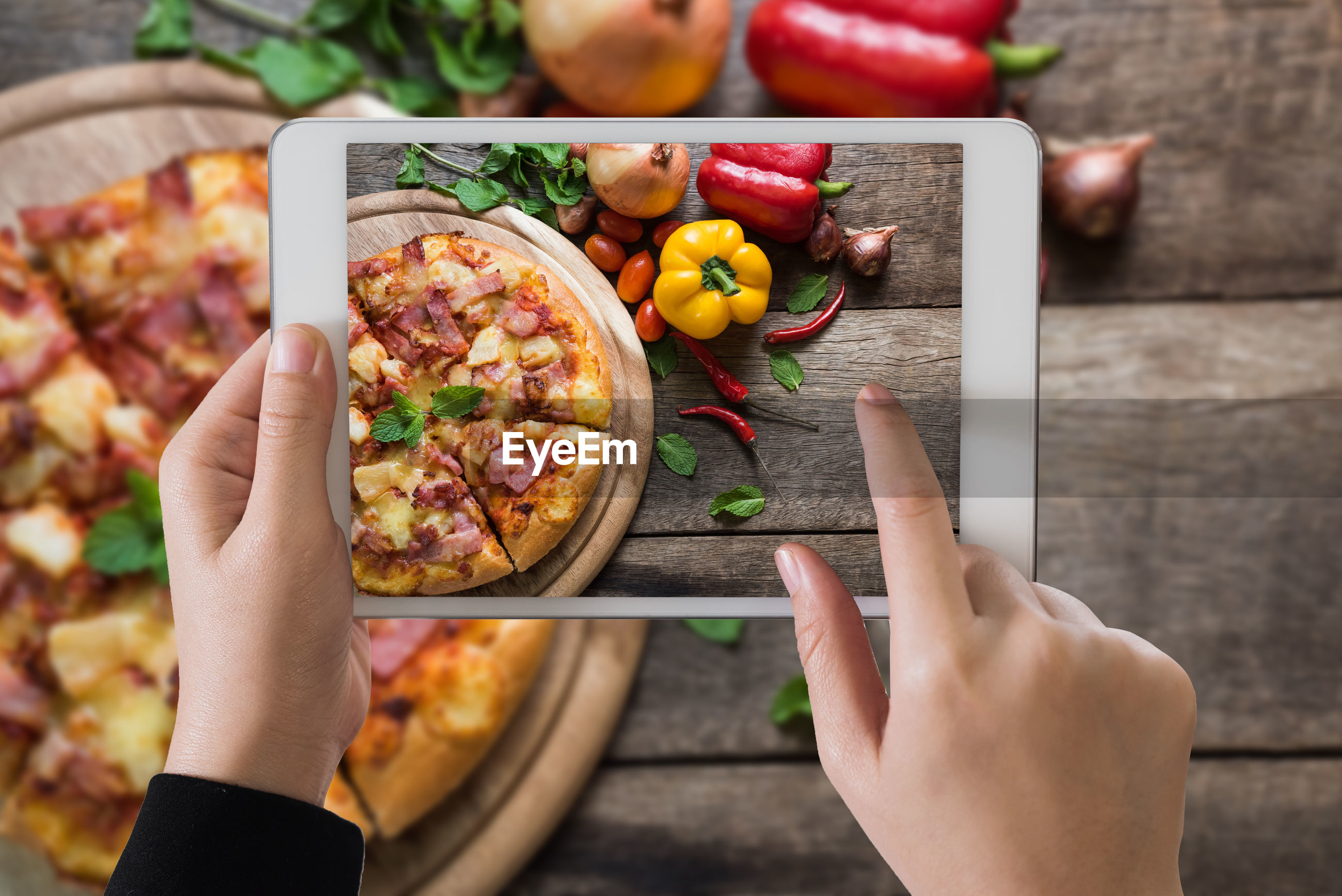 Cropped hand of woman photographing food from digital tablet on table