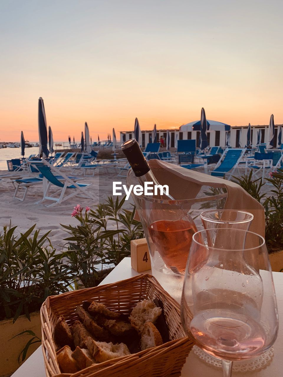 sky, water, sunset, glass, drink, food and drink, refreshment, nature, table, sea, no people, wine, nautical vessel, beach, orange color, alcohol, wineglass, drinking glass, mode of transportation, outdoors