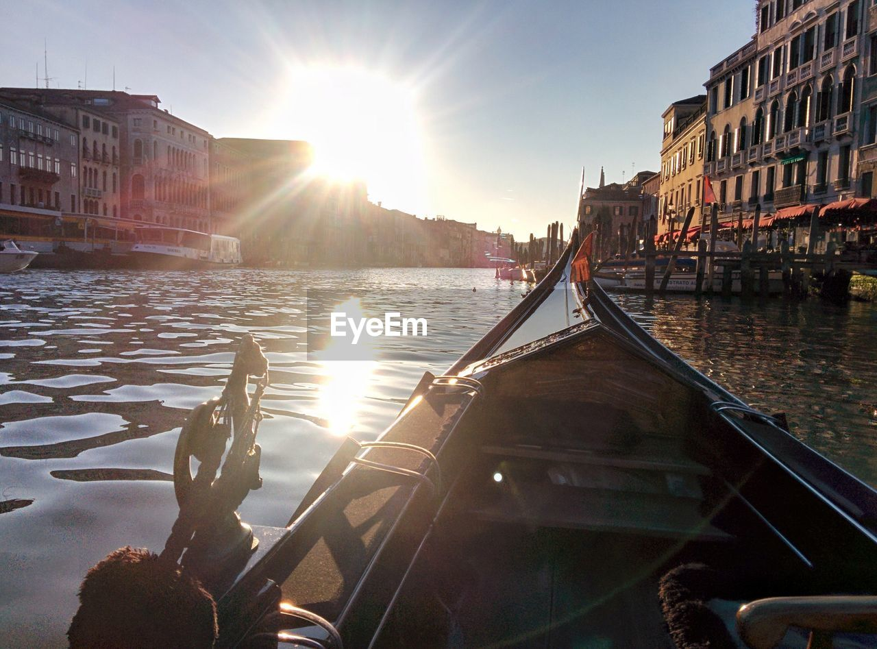 water, architecture, sunlight, sky, sunbeam, nautical vessel, built structure, transportation, building exterior, mode of transportation, nature, lens flare, sun, city, canal, reflection, day, travel destinations, sunset, outdoors, no people, bright