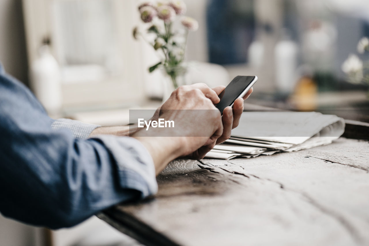 MIDSECTION OF MAN USING PHONE ON TABLE