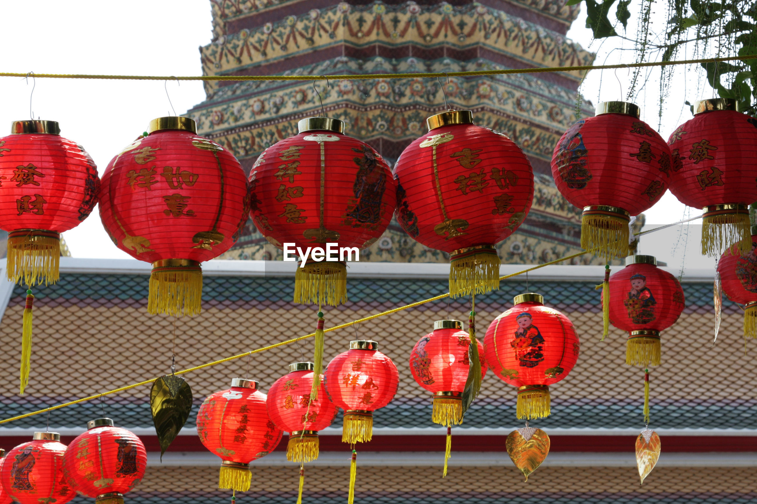 Chinese lanterns hanging by temple against sky