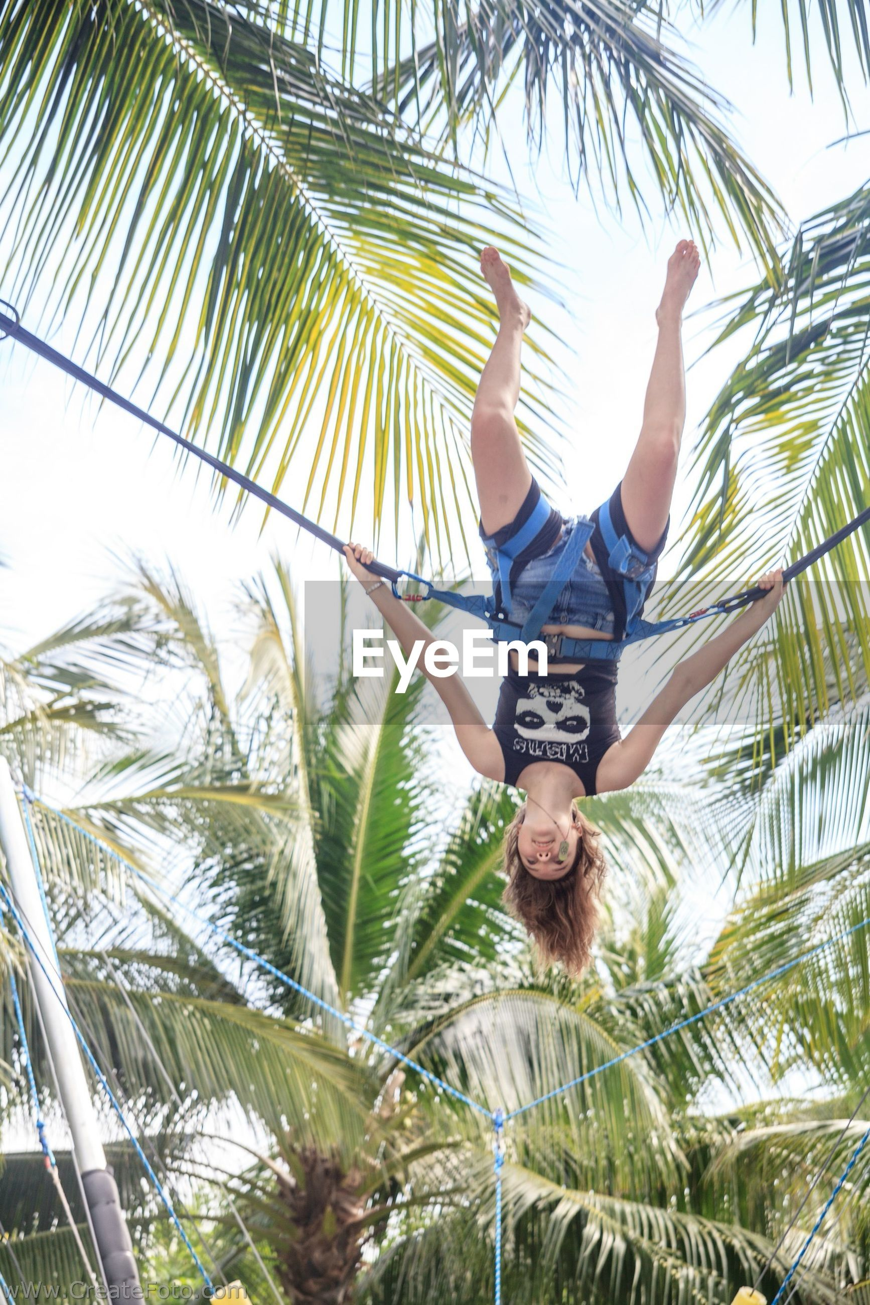 tree, low angle view, palm tree, leisure activity, lifestyles, person, young adult, clear sky, growth, looking at camera, sky, front view, day, casual clothing, portrait, nature, branch, smiling