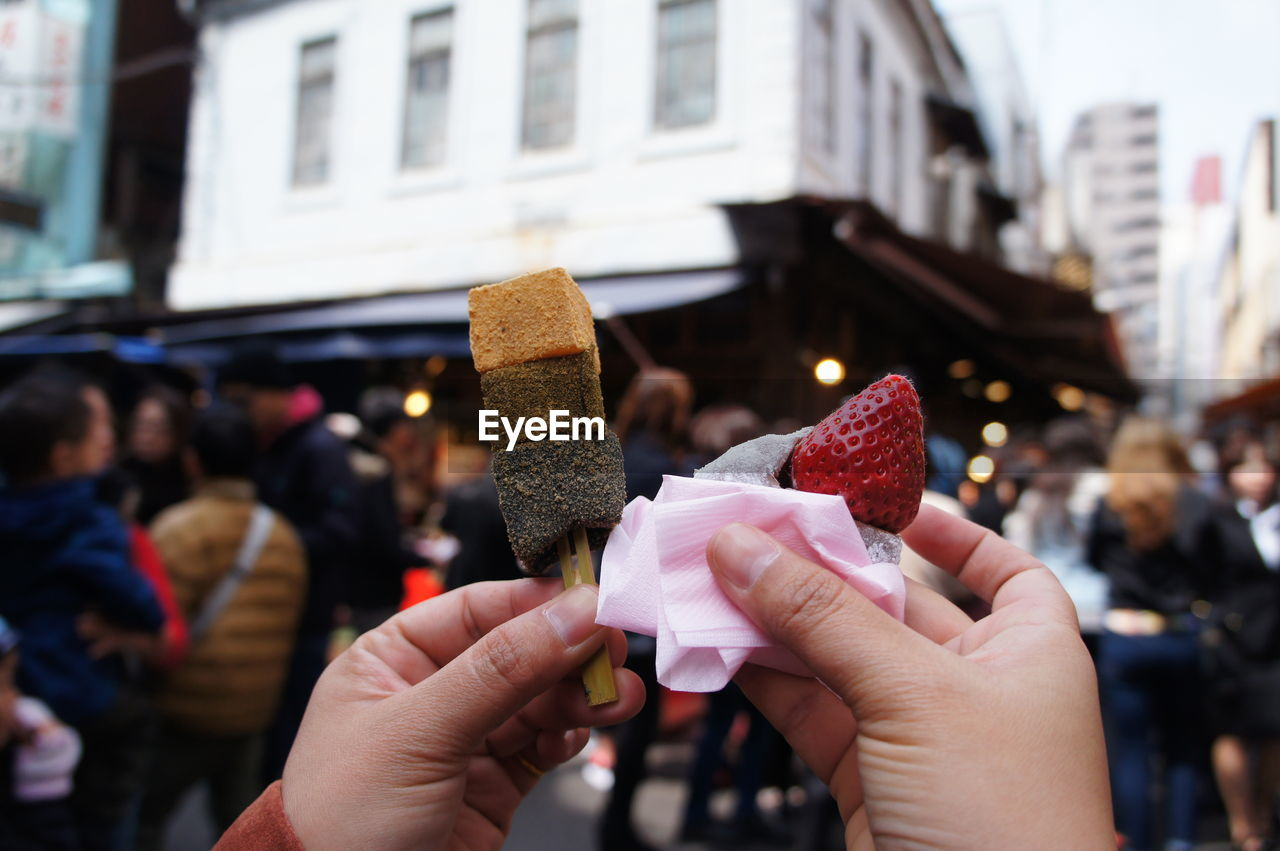 Cropped Image Of Hands Holding Dessert And Fruit In City