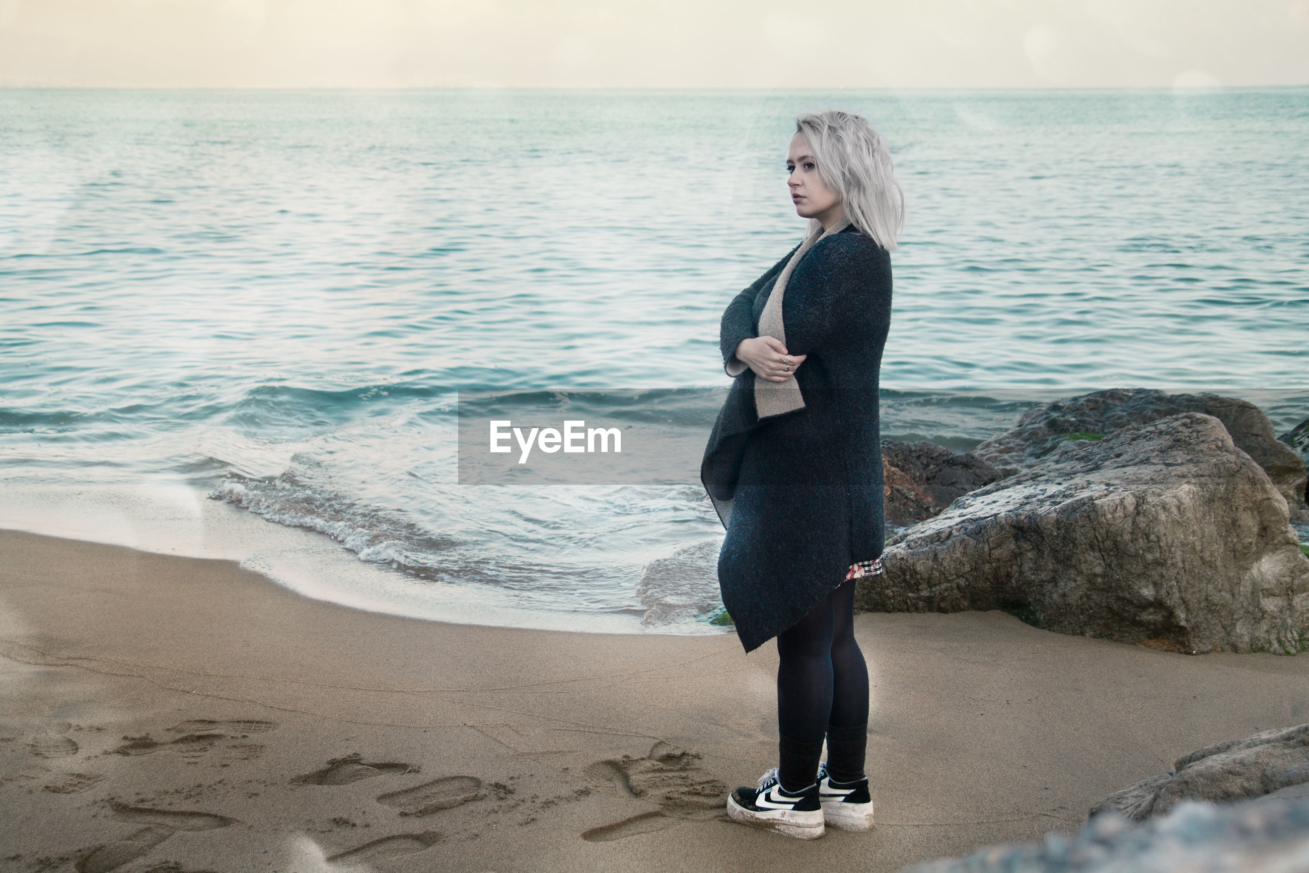 Full length side view of thoughtful young woman wearing winter coat while standing on shore at beach