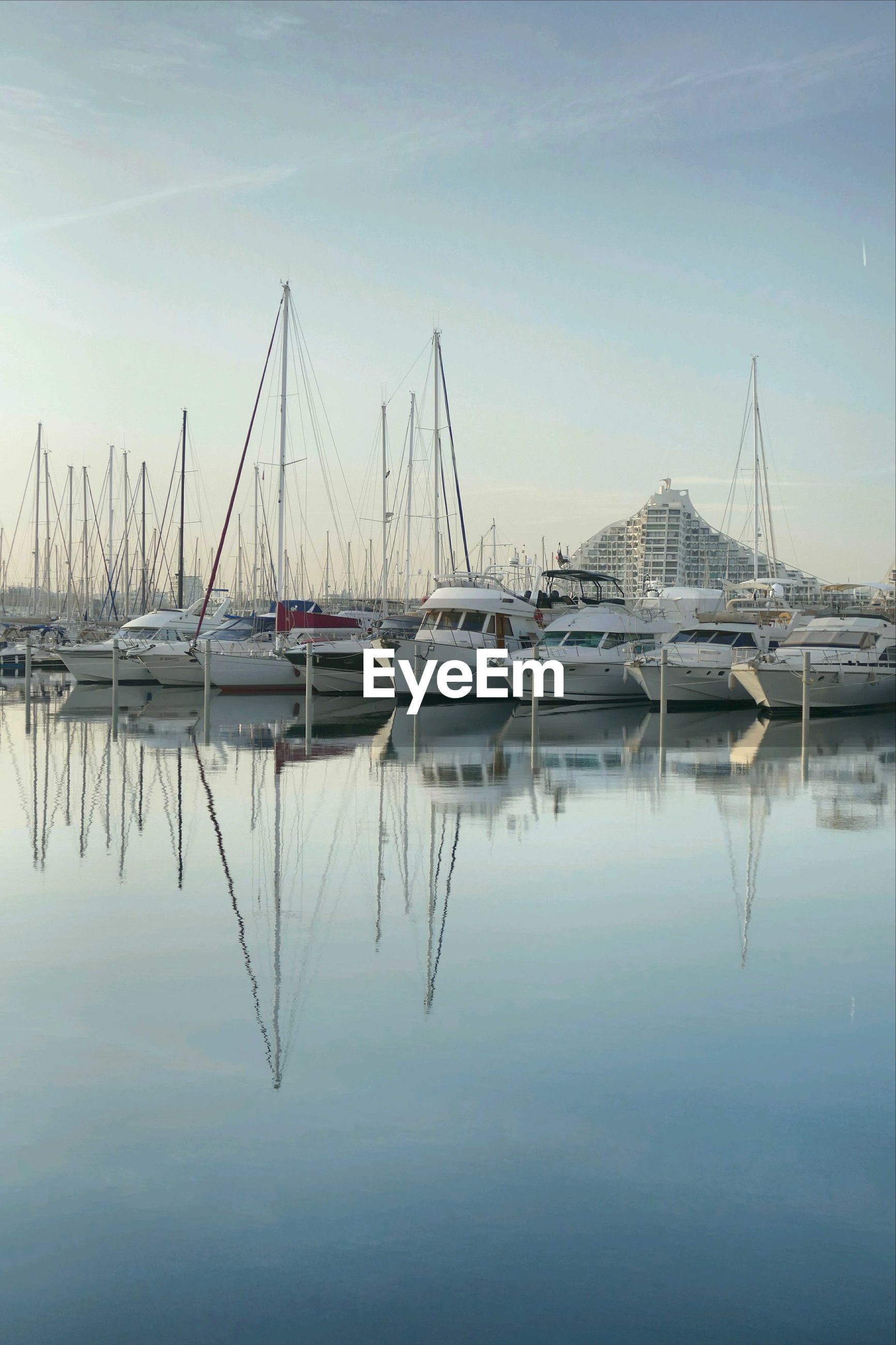 reflection, water, sky, moored, transportation, mode of transport, harbor, nautical vessel, no people, built structure, outdoors, standing water, building exterior, nature, architecture, day, mast, tree, sailboat, yacht