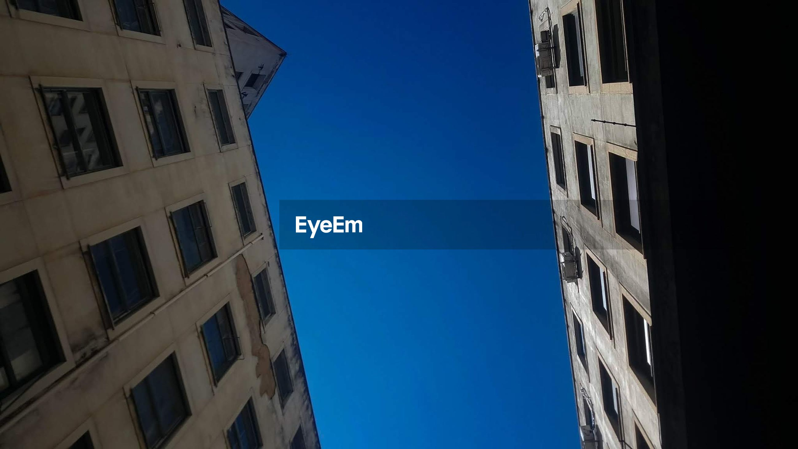 LOW ANGLE VIEW OF RESIDENTIAL BUILDING AGAINST BLUE SKY