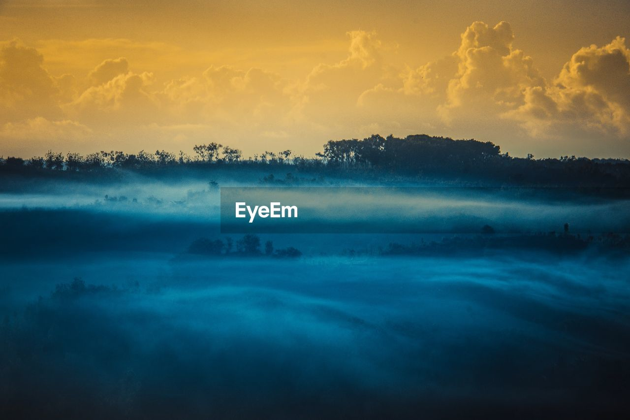 sky, cloud - sky, beauty in nature, scenics - nature, tranquil scene, tranquility, sunset, idyllic, no people, fog, nature, orange color, non-urban scene, outdoors, majestic, hazy, environment, landscape, dramatic sky