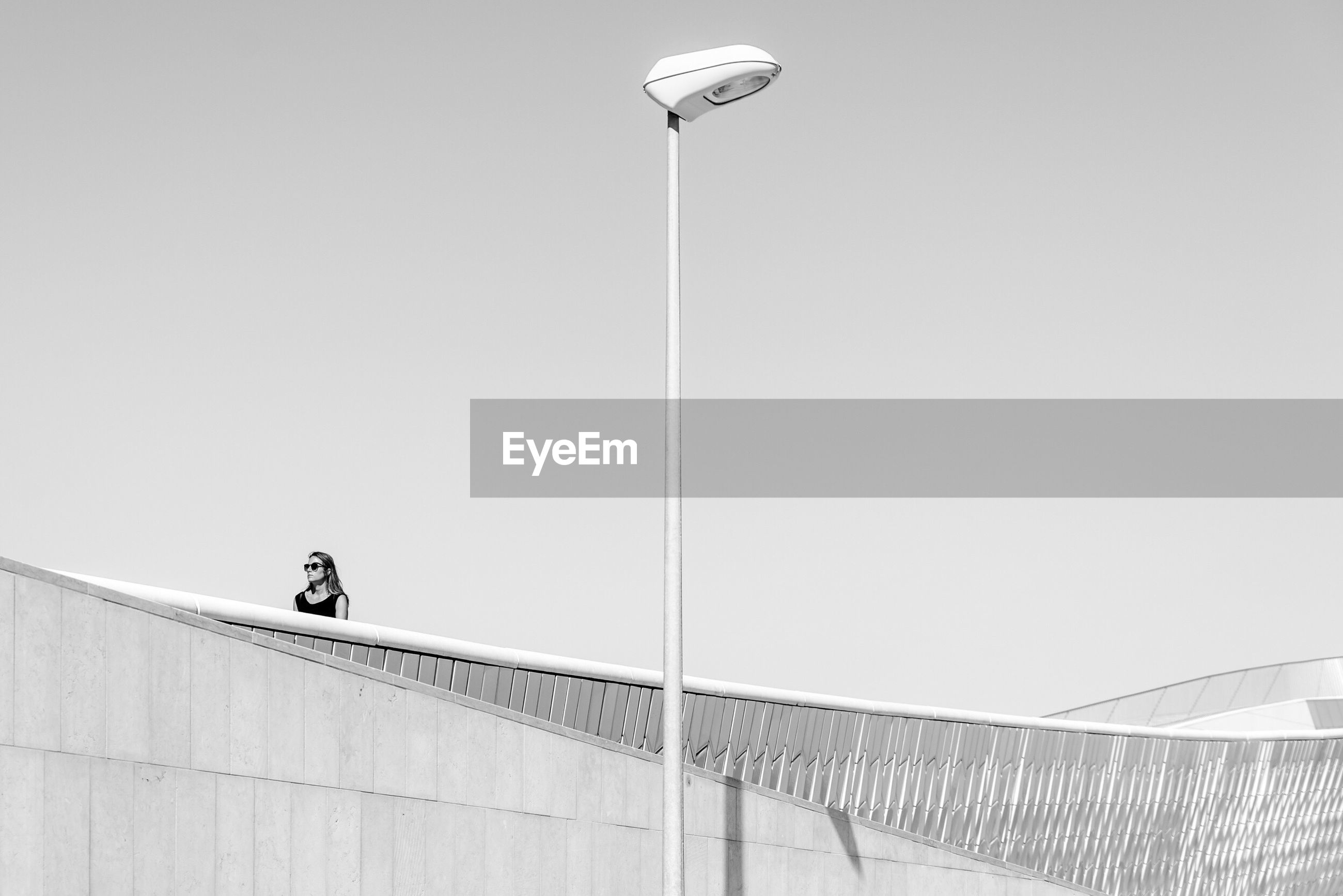 LOW ANGLE VIEW OF WOMAN ON STREET LIGHT AGAINST CLEAR SKY