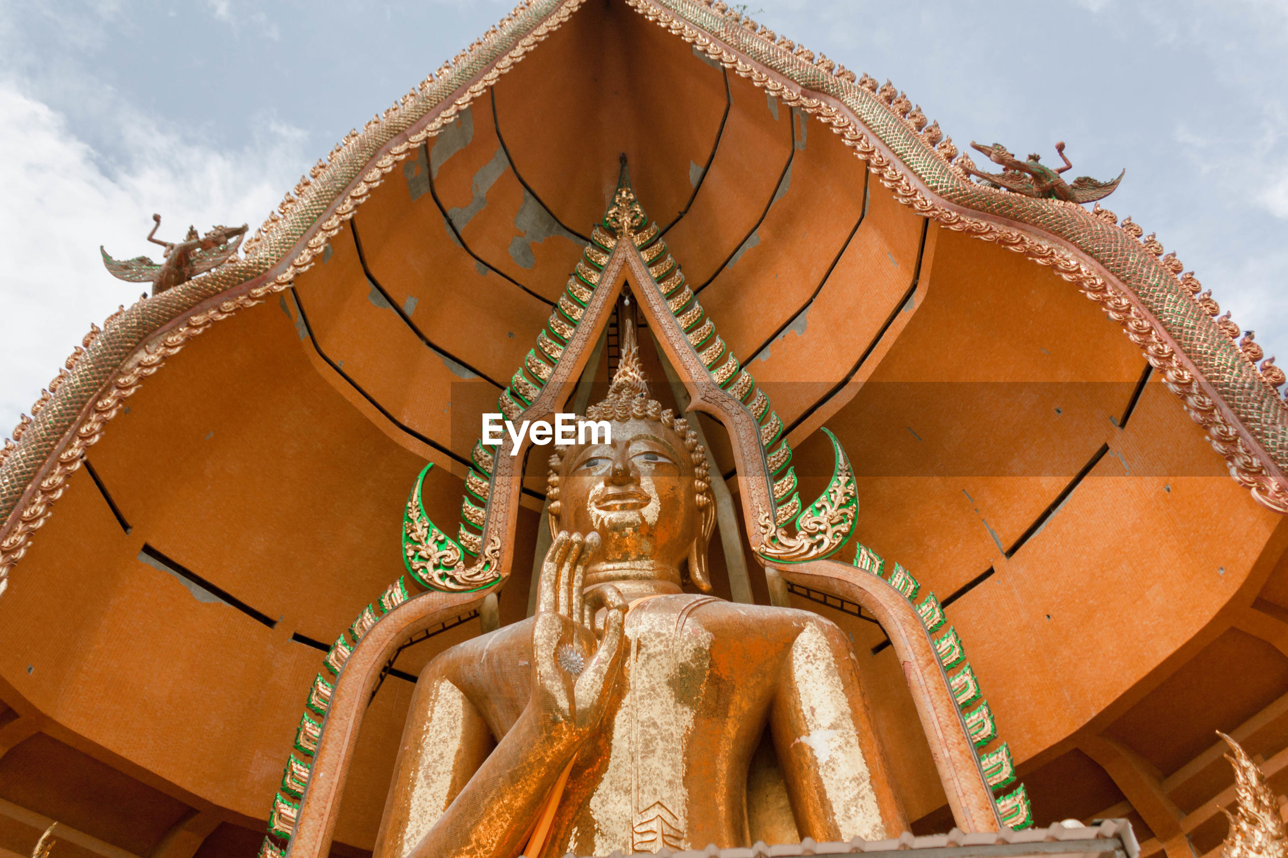 Low angle view of buddha statue in temple against sky