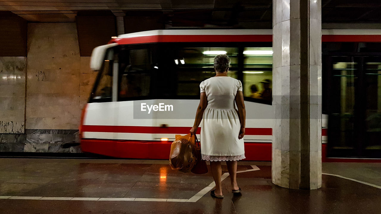 Rear view of woman standing on bus