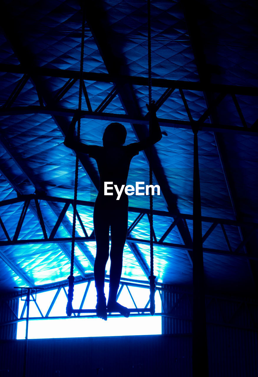 low angle view, indoors, silhouette, one person, architecture, built structure, full length, day, standing, real people, people