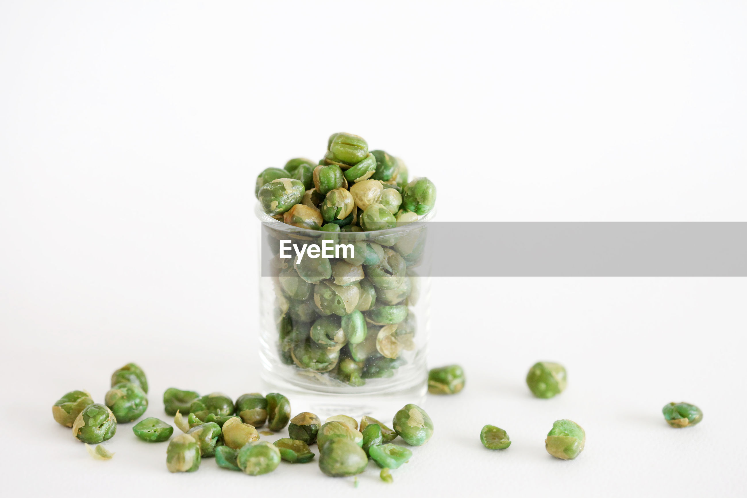 Close-up of green pea in glass against white background