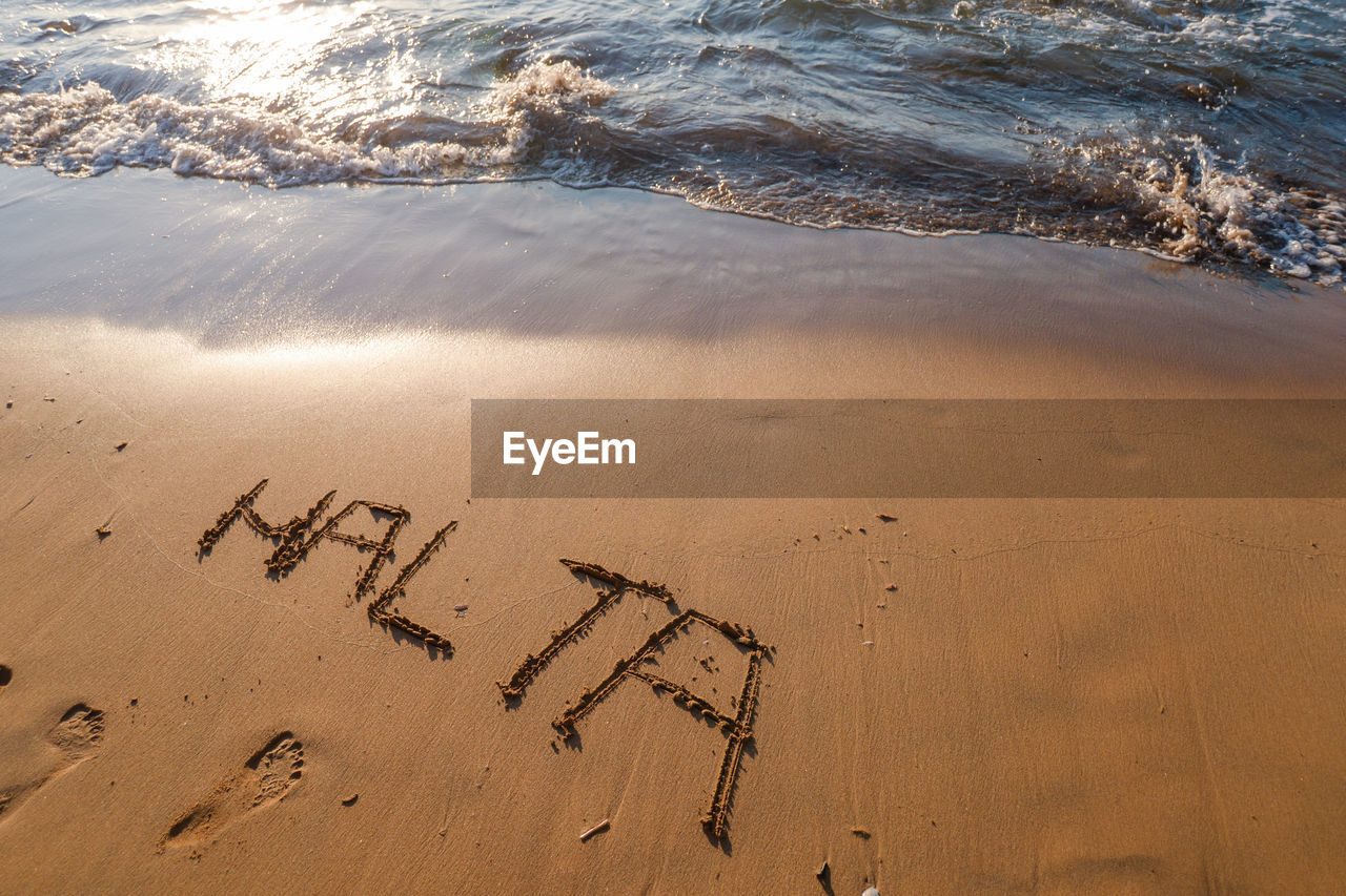 HIGH ANGLE VIEW OF TEXT WRITTEN ON BEACH