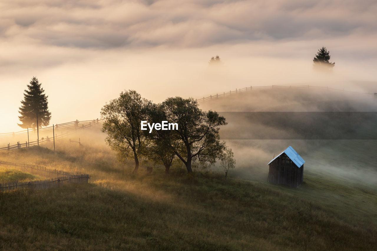 Hut on mountain against cloudy sky