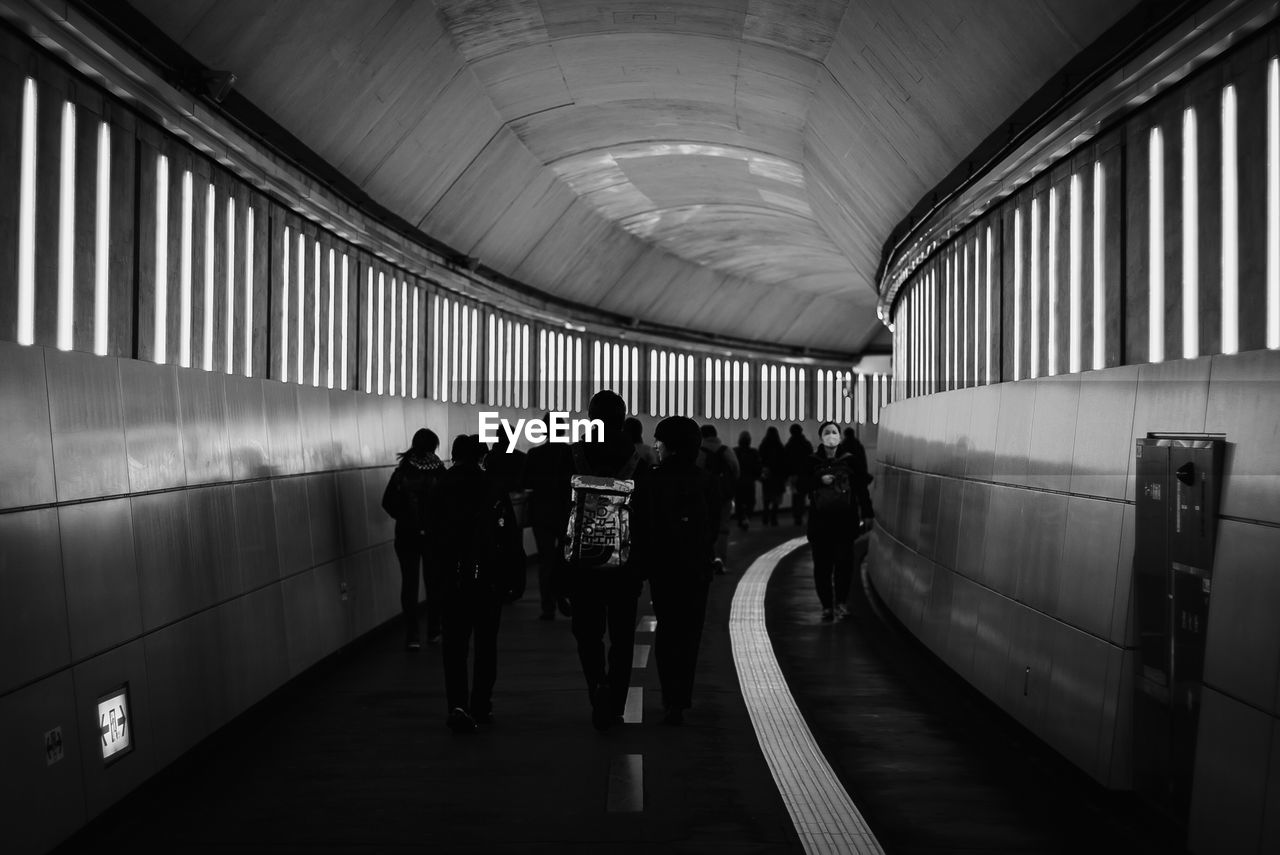 group of people, public transportation, indoors, transportation, real people, architecture, men, rail transportation, women, mode of transportation, large group of people, travel, subway station, subway, lifestyles, crowd, built structure, ceiling, flooring, track, waiting, underground walkway