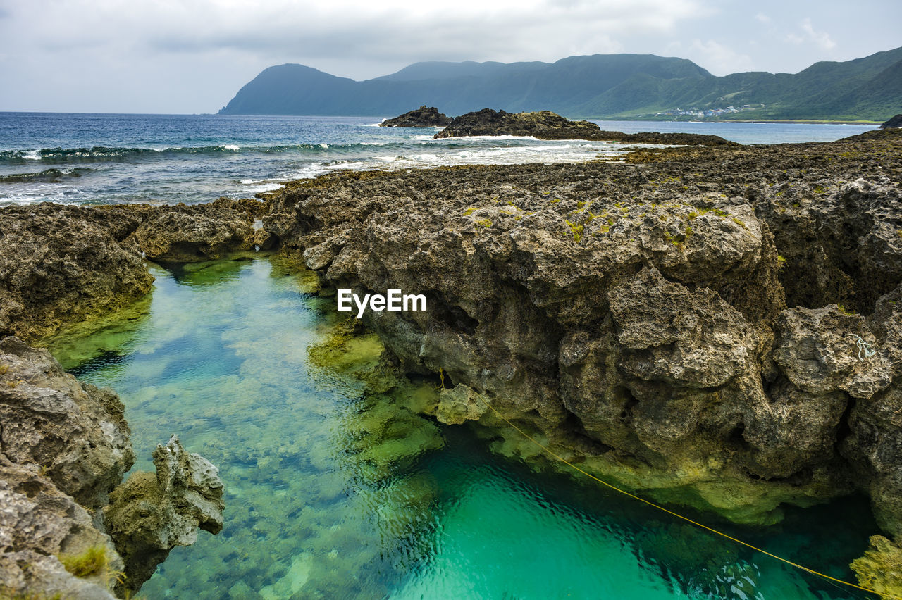 water, sea, rock, beauty in nature, scenics - nature, solid, rock - object, tranquil scene, nature, sky, tranquility, day, land, no people, motion, mountain, non-urban scene, idyllic, outdoors, turquoise colored, lagoon, power in nature