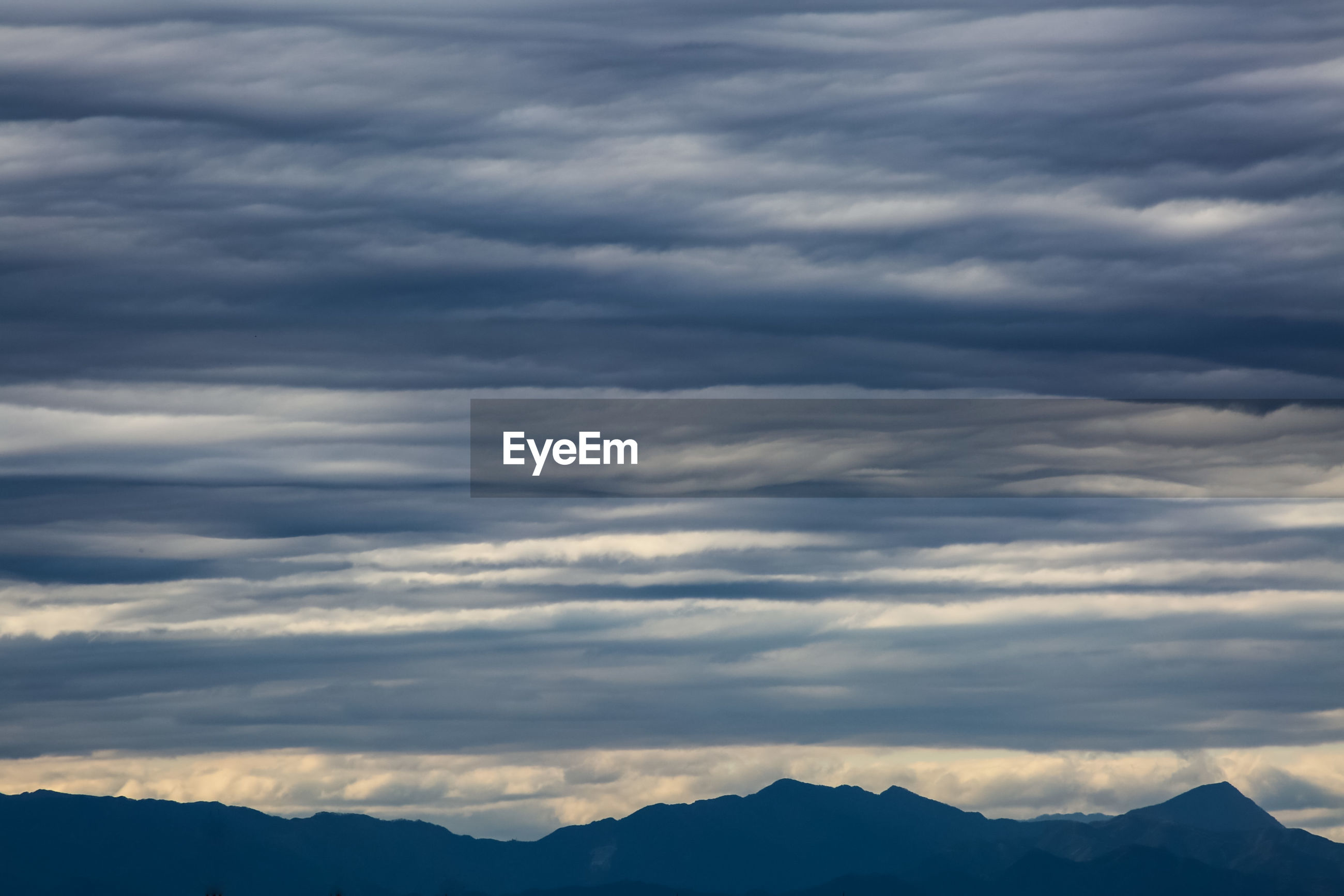 LOW ANGLE VIEW OF MOUNTAINS AGAINST SKY AT SUNSET