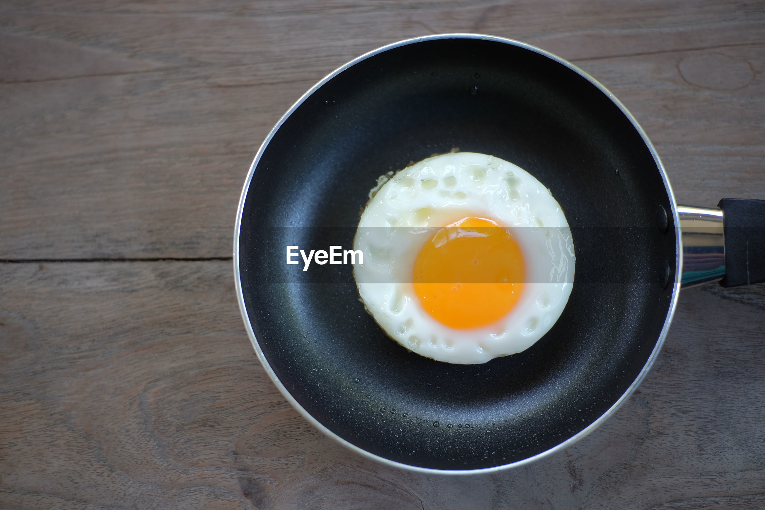 Directly above shot of fried egg in pan on table
