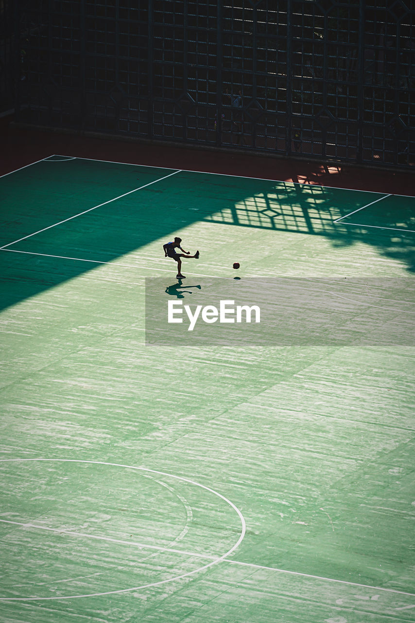 sport, real people, leisure activity, one person, court, lifestyles, playing, high angle view, full length, healthy lifestyle, men, competition, playing field, day, athlete, outdoors, tennis, nature, stadium, match - sport
