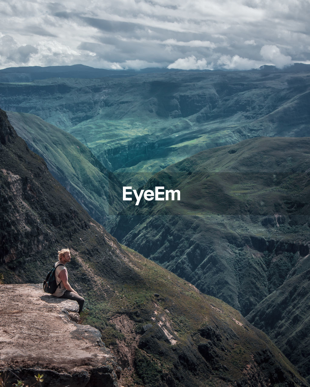 mountain, leisure activity, scenics - nature, beauty in nature, sitting, one person, lifestyles, tranquility, cloud - sky, non-urban scene, real people, tranquil scene, sky, nature, mountain range, vacations, holiday, environment, trip, adventure, looking at view, outdoors