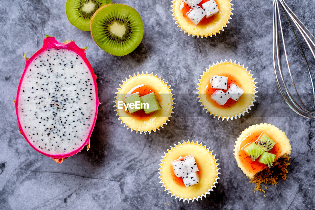 food and drink, food, freshness, healthy eating, sweet food, indoors, cupcake, fruit, sweet, high angle view, directly above, dessert, still life, kiwi, cake, indulgence, kiwi - fruit, no people, table, choice, temptation, cupcake holder, snack