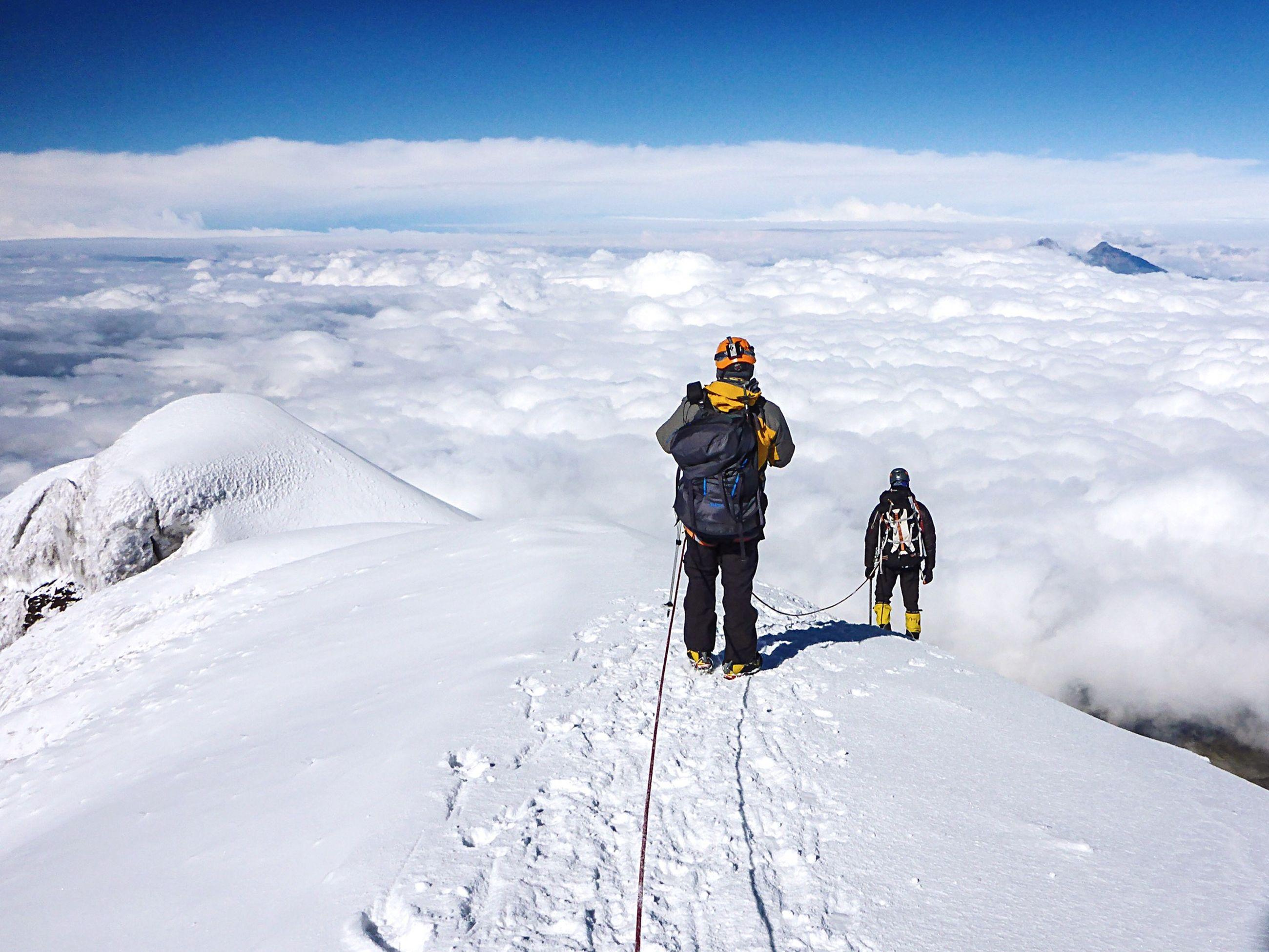Mountain climber walking on snow covered mountain