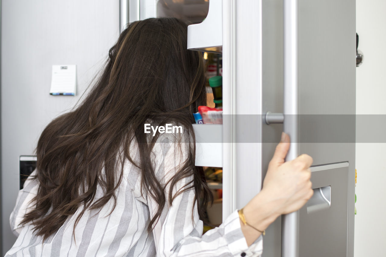 Rear View Of Woman Searching In Refrigerator